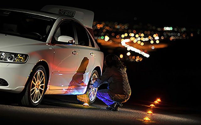 Balizas de emergencia en la carretera de Stonepoint colocadas en la carretera detrás de una mujer que arregla un neumático pinchado en un automóvil blanco por la noche.