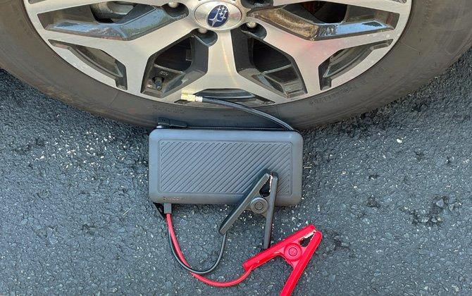 Se muestra Mophie Powerstation Go Rugged con compresor de aire con cables de puente delante de la llanta de un automóvil.