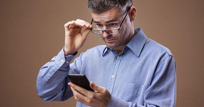 Man Using Reading Glasses Phone 700px